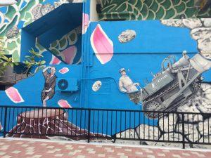 沖縄市の古民家民宿ごーやー荘から近いコザ十字路巨大壁画。戦後米軍に史跡を破壊された様子を描く。下町散歩でホテルとは違った宿泊スタイルで沖縄旅行を楽しむ。