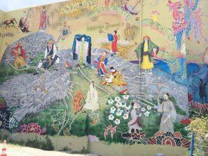 沖縄市の古民家民宿ごーやー荘から近いコザ十字路巨大壁画には琉球王国時代の様子が描かれている。下町散歩でホテルとは違った宿泊スタイルで沖縄旅行を楽しむ。